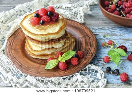 Plate with delicious pancakes and berries on table, close-up