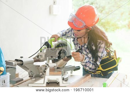 Asian pretty female carpenter using Electric Sander for wood. poster