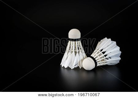Badminton balls over black background Sports and recreation concepts.