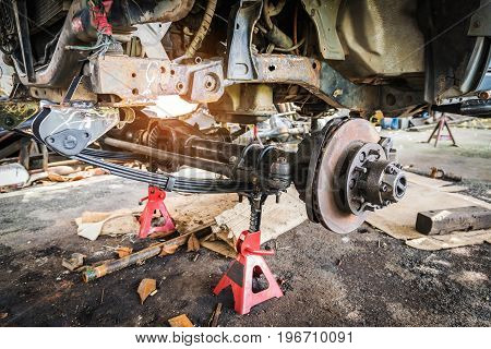 Old and rusty car's suspension which removes the wheels for repair replacement and change news parts -Automotive industry and garage concepts.