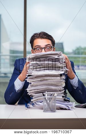 Businessman with pile stack of paper paperwork in the office