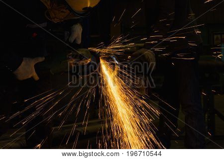 Close-up worker hand using electric wheel grinding on steel structure in factory.