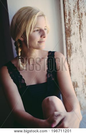 Woman portrait at home. Long blonde hair and pigtail. Female looking out of window.