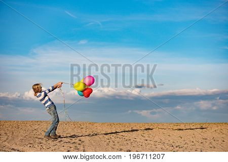 Birthday girl with colourful balloons outdoors, windy weather