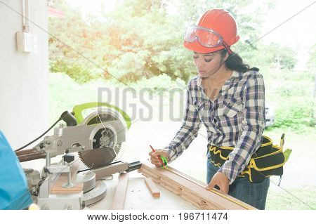 Pretty Asian carpenter woman is marking on wood for cut.