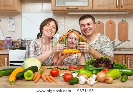 Family cooking in kitchen interior at home, fresh fruits and vegetables. Healthy food concept. Woman, man and children. Making house shape from vegetables.