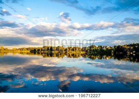 Summer evining sky and clouds reflection in water