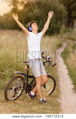 Attractive young guy with road bicycle outdoors. Guy wearing white T-shirt and jeans shorts with headphones on the head and his hands up. Cycling along country trail outdoor. Riding in the countryside. Healthy active lifestyle.