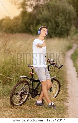 Attractive young smiling guy with road bicycle outdoors. Guy wearing white T-shirt and jeans shorts with headphones on the head and shows thumb up. Cycling along country trail outdoor. Riding in the countryside. Healthy active lifestyle.