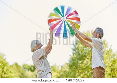 Seniors playing with a big ball in summer in the nature
