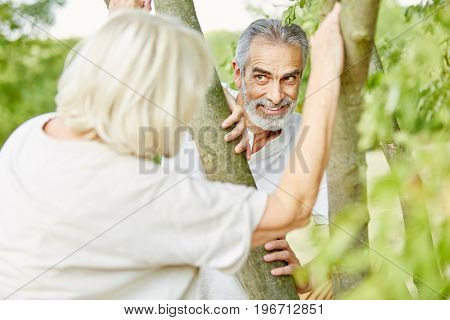 Senior couple flirting and playing hide and seek in summer in the nature