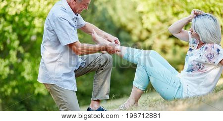 Senior man helps senior woman with sprained anke in the nature