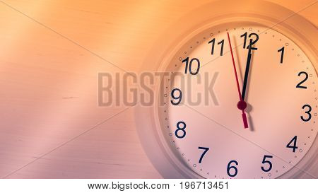 Clock hanging on wall ticking showing twelve hours
