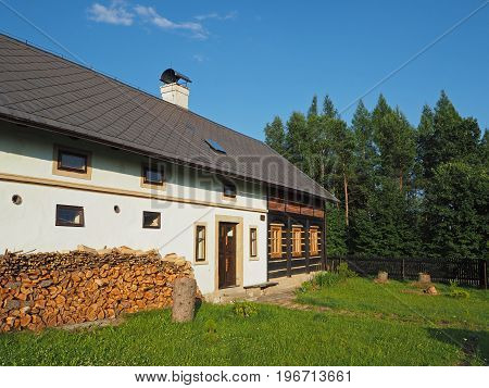 half timbered masonry old rustic house with chopped wood and green grass