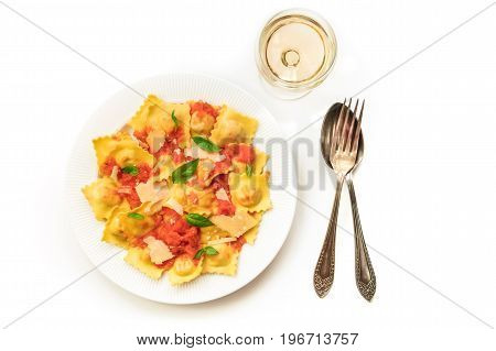 An overhead photo of a plate of ravioli with tomato sauce, grated Parmesan cheese, and basil leaves, shot from above on a white background with a glass of wine, a fork and a spoon, with copy space