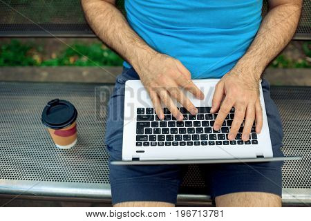 Close-up shot of handsome man's hands touching laptop computer's screen. Businessman using a laptop computer and sitting on a bench.