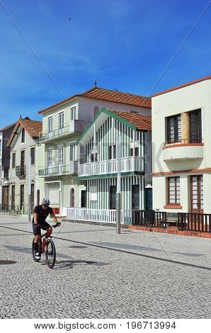 Costa Nova Portugal - June 09 2017: Cyclist on the bicycle in famous resort on the Atlantic coast in Beira Litoral. Popular tourist destination to spend vacation time