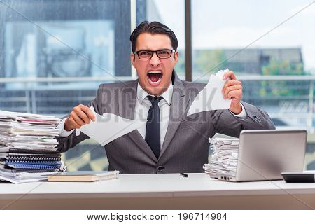 Angry businessman with too much work in office