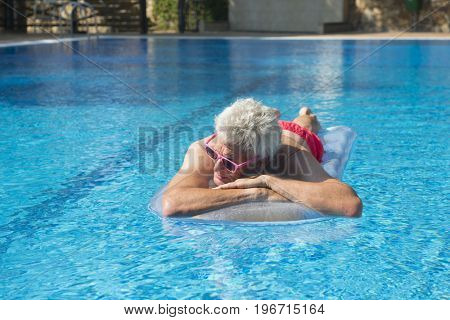 Senior man on vacation floating on water in swimming pool