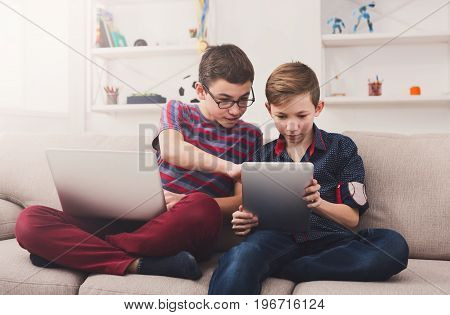 Two male kids with gadgets. Sharing photos on laptop and digital tablet, discussing them on sofa at home. Boy friendship and communication concept