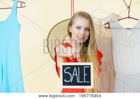 Woman in clothes shop store holding black board with sign sale picking summer perfect outfit dress hanging on clothing hangers
