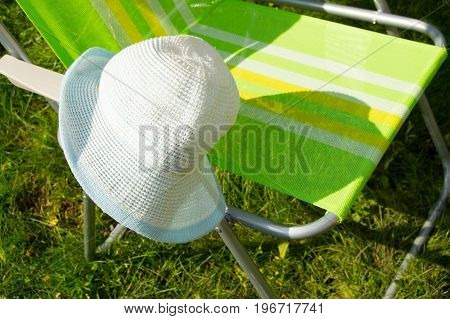 Folding Stool For Camping And Hat, The Background Of Green Grass