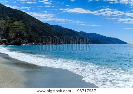 Gravel beach near walking trailing through Cinque Terre villages in Italy. Focus on foam waves sea.