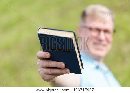 guy giving book by one hand to camera
