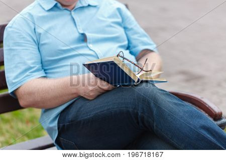 Man reading on bench. Book in his hands