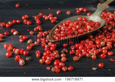 pink pepper lay on wooden table in spoon