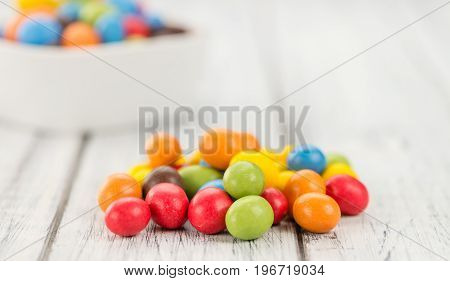 Portion Of Cocolate Coated Peanuts On Wooden Background (selective Focus)