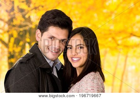 Close up of beautiful young couple in love in st valentines day in a blurred autum park background.