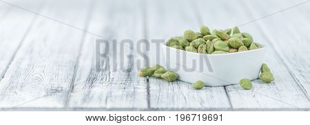 Portion Of Wasabi Coated Peanuts On Wooden Background (selective Focus)