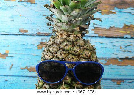 Pineapple fruit with blue  sunglasses/ Pineapple fruit with blue  sunglasses in front of scraped blue planks.