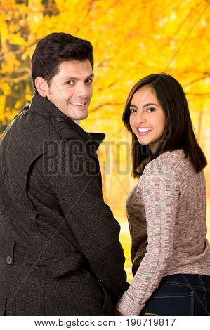 Beautiful young couple in love in st valentines day holding their hands in a blurred autum park background.