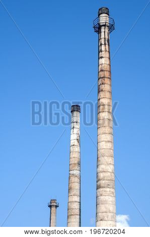 Abandoned and crumbling vintage obsolete industrial chimneys on blue sky background