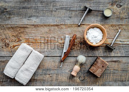 Barbershop. Men's shaving and haircut. Brush, razor, foam on wooden table background top view.