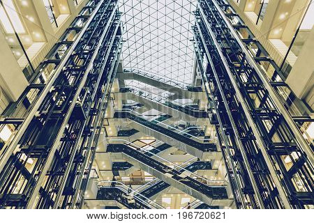 Lifts and escalators in a modern building, interior view of modern shopping mall, toned