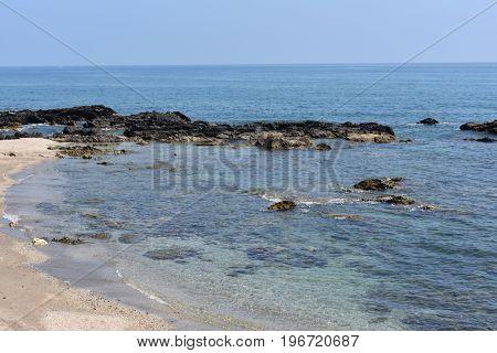 The beach looks blue and has some rocks near the shore