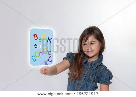 Long hair smiling little girl is touching by her index finger a transparent rectangle with inscription back to school . All is on the light gray background.