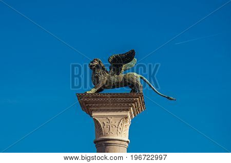 Close-up of column with the winged lion, symbol of Venice, and blue sunny sky in Piazza San Marco. At the city of Venice, the historic and amazing marine city. Located in Veneto region, northern Italy