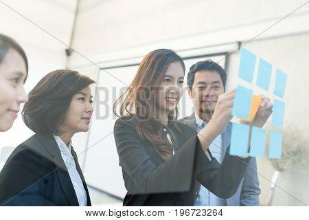 Businesswoman sticking memo on glass