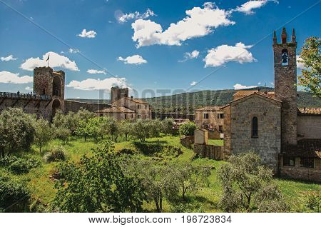 View of buildings, belfry and trees from above the walls of the Monteriggioni hamlet. A medieval fortress, surrounded by stone walls, at the top of a hill, near Siena. Located in the Tuscany region