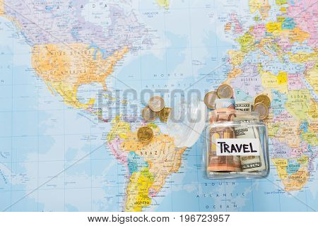 Travel budget concept. Money saved for vacation in glass jar on world map background, top view, copy space. Banknotes and coins for big adventure.
