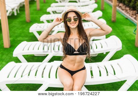 Side View Of Woman Sunbathing By The Swimming Pool