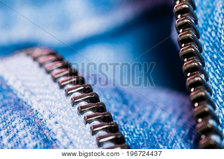 A closeup view of fastener of light blue jeans. Good visible texture and pattern.