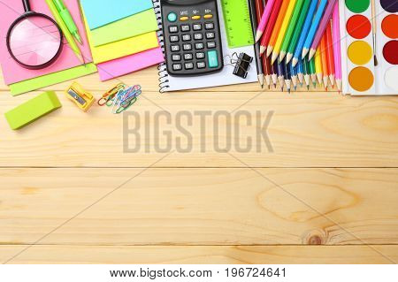school and office supplies. school background. colored pencils, pen, pains, paper for  school and student education on wooden background. top view with copy space