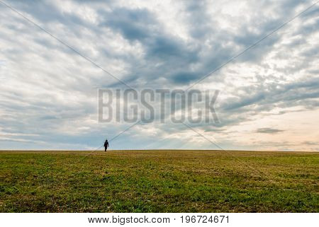 A lonely man walking on the horizon of the landscape under a dramatic looking sky. Feeling loneliness and fear. HDR shot.