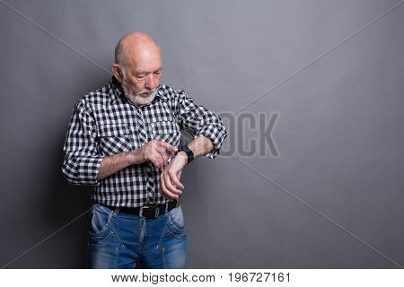 Serious senior man clicking on screen of his smart watch, gray studio background, copy space
