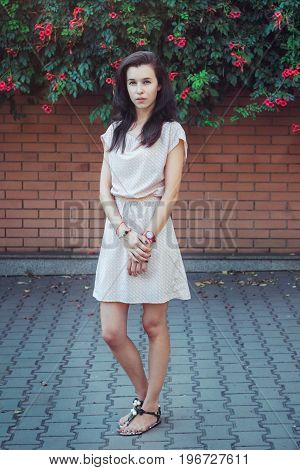 Full length portrait of beautiful young brunette woman, wearing short casual dress, standing in front of brick wall covered by blooming trumpet creeper plant. Street  fashion.